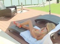 Seductive blonde with amazing legs is relaxing in the lounge chair