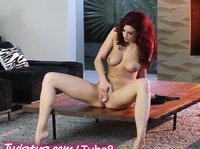 A busty redhead fingers her wet slit