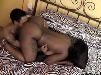 A black couple are doing their thing on zebra sheets