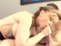 A busty milf sucks a young cock into her mouth up to the balls
