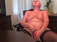 A blonde granny is toying herself on the chair