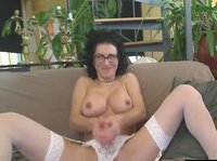 A nerdy girl on the couch is being really nasty: she is not shy to spread her long legs before sucking on her favorite dildo