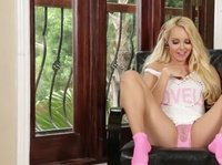 A blonde teen cutie in pink socks plays with herself on a black chair