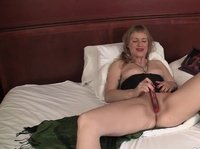 A mature blonde is toying her neatly trimmed pussy