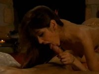 A brunette swallows a dick by a fireplace